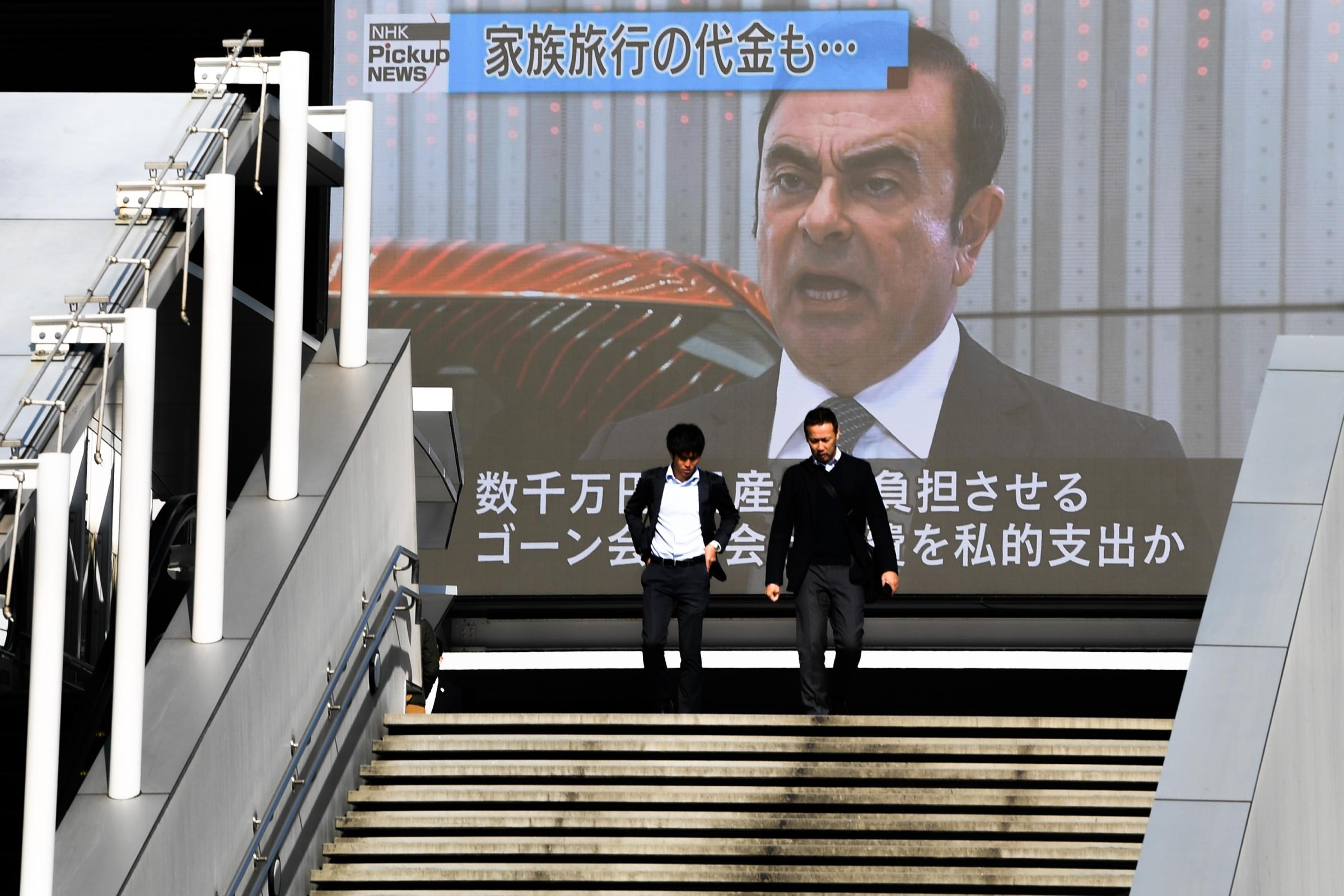 Pedestrians next to a screen showing Carlos Ghosn. Photograph: Getty